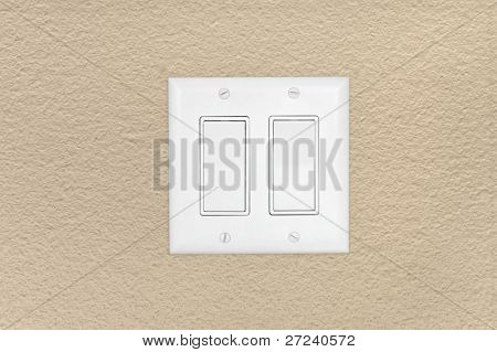 A 110 volt white modern light power switch on a beige wall