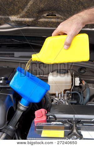 A mechanic pours fresh oil into a car engine as part of its maintenance.