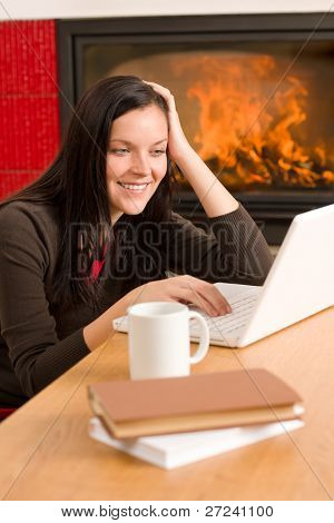 Happy woman at fireplace with laptop enjoying winter hot drink