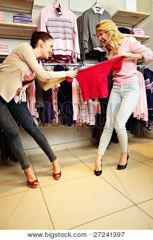 Foto de dos chicas codiciosas luchando por rojo tanktop en almacén