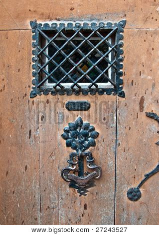 Fragment of an old wooden door with a shod lattice