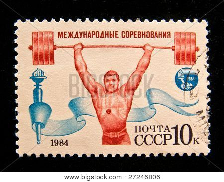 USSR - CIRCA 1984: A stamp printed in the USSR shows Soviet weightlifter holds the barbell over your head, circa 1984