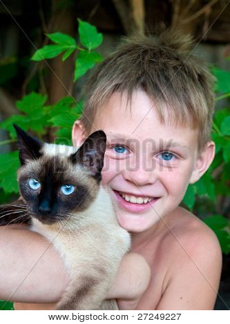 blue-eyed boy holding a Siamese cat. Focus on the cat's eyes