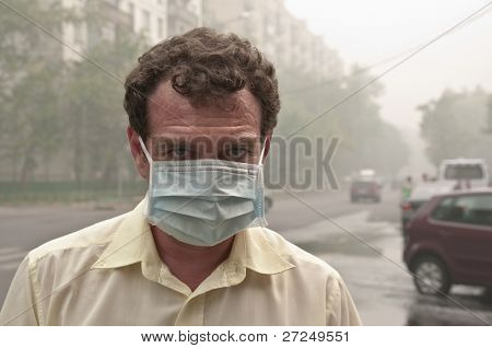 Smog in the city. A men in medical mask