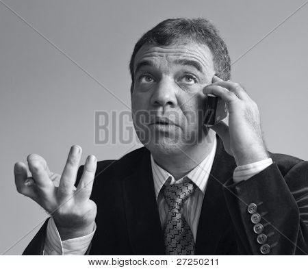Unpleasant conversation. The businessman speaks by phone. Black-and-white portraits a series.