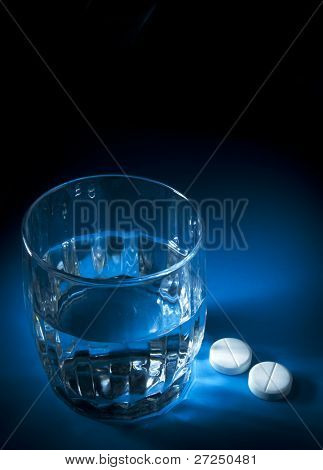 Glass of water and two aspirin tablets in a blue light