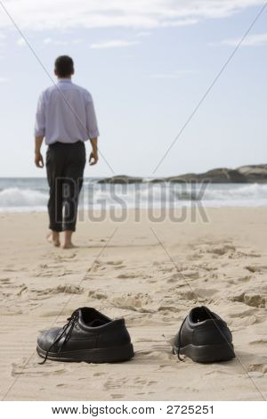 Manager Walking Barefoot On The Beach