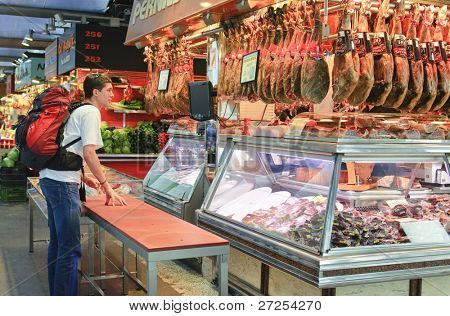 BARCELONA - JUNE 29: An unidentified tourist buys jamon in the La Boqueria market on June 29, 2011 in Barcelona, Spain. La Boqueria is one of the oldest markets in Europe that still exists. It was established in 1217.