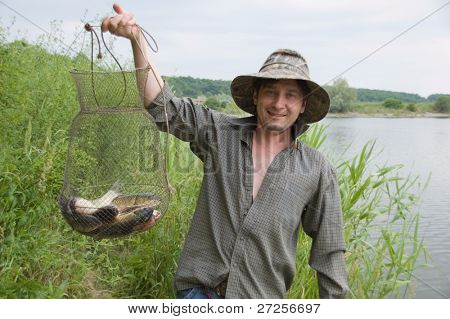 happy fisherman with his catch in the rushy lake