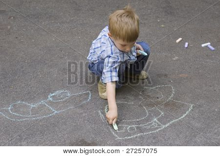 child drawing on asphalt car