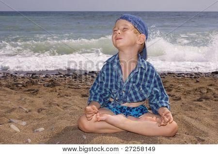 3 years old yogi boy relaxing on the beach