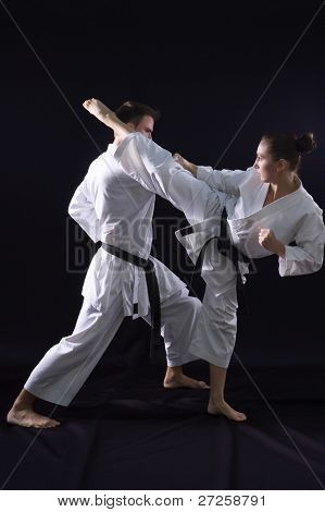 fighting karate couple - champions of the world - on black background studio shot