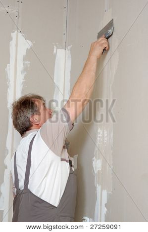 man putty plasterboard indoor