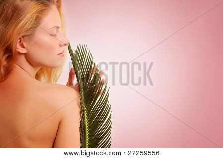 beautiful young woman with plant over pink background