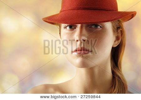elegant young woman with red hat over light background