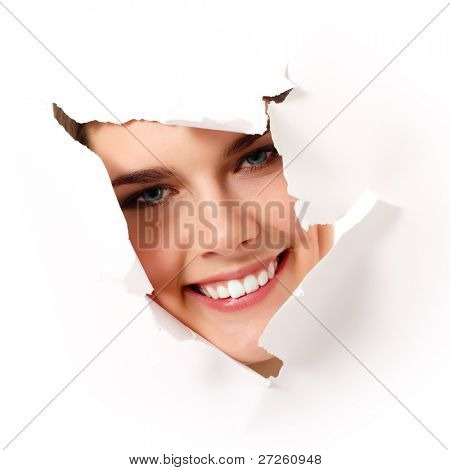 cheerful teen girl peeping surprised through hole in paper
