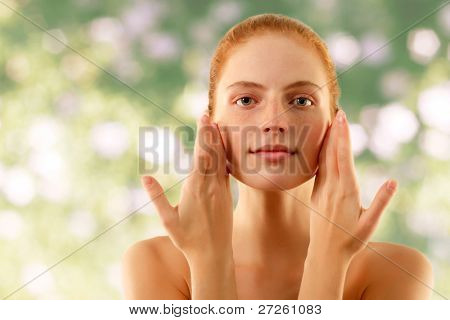 summer woman young beautiful no make-up touching face with her hands over nature background