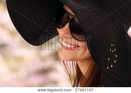 spring teen girl cheerful in panama and  sunglasses enjoying over blossom pink green nature background