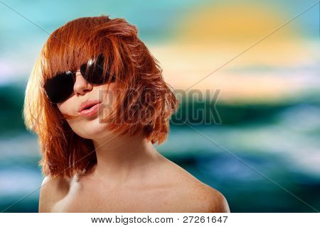 summer teen girl red-haired cheerful in sunglasses enjoying over sea sunset background