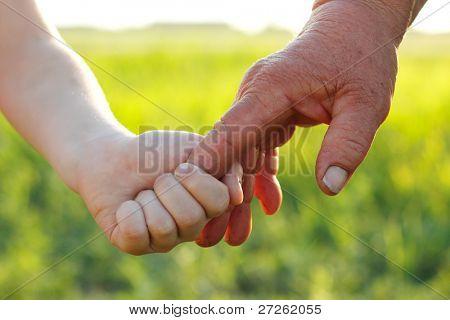 Hände Kind und alten Senior überarbeitet über Natur Sommer Weizenfeld