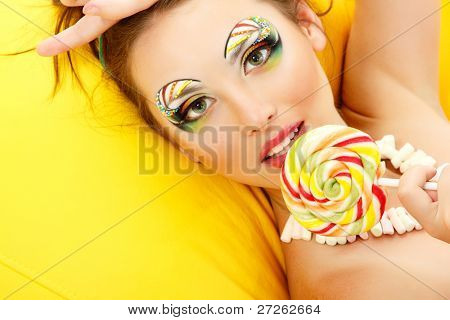 woman licks candy with beautiful make-up