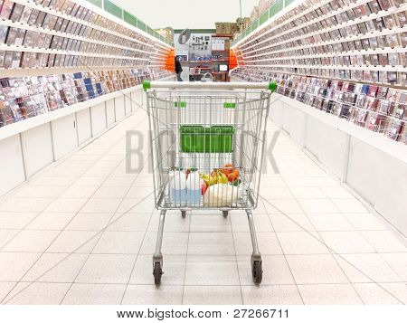 shopping trolley with purchases in the supermarket. Focus is under the back site of trolley
