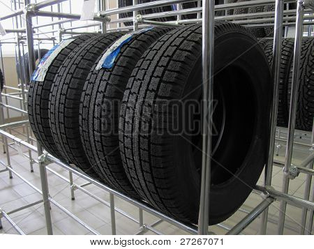 The image of car wheels stands on the shelves at the warehouse