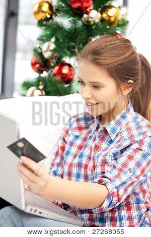 happy Woman with Laptopcomputer und Kreditkarte über Weihnachtsbaum