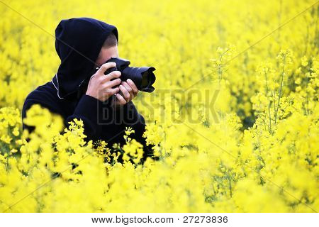 Nature photographer at work in a field of flowers