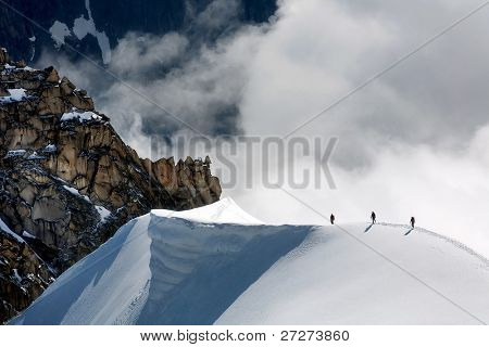 Team of three alpinists climbing a mountain