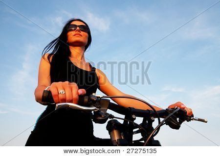 Portrait of a pretty young brown haired woman riding a bike - sunset light