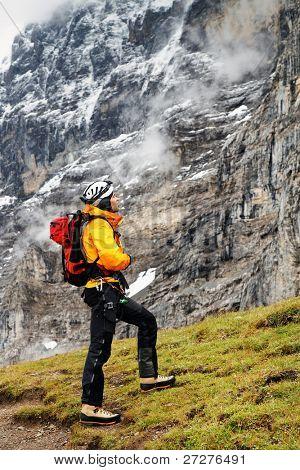 Alpinist contemplating the Eiger North Face, Berner Oberland, Switzerland