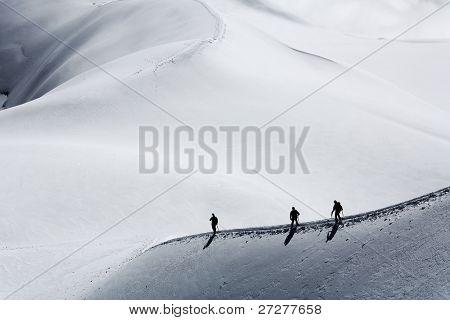 Equipo de tres alpinistas escalar una montaña