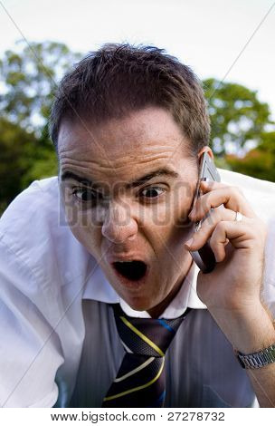 Angry business man yelling on the phone