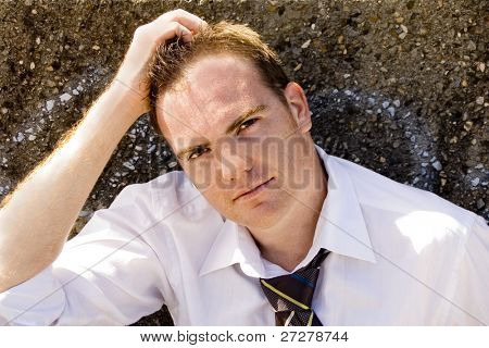 Young casual business man or student leaning against a grafitti wall in the city