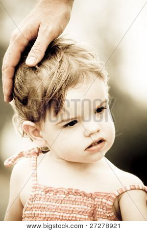 cute toddler with her dad's hand patting her  on the head