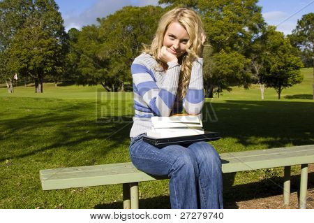 Beautiful young student holding books