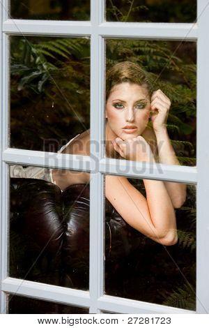 Retrato de una bella modelo tendida en el sofá mirando por la ventana