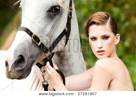 Beautiful young woman leading a grey horse in the country