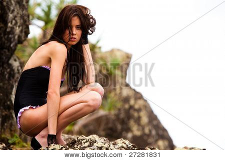 An attractive young woman wearing a black one-piece swimsuit, black lace gloves, and high heels is crouching on a rock formation. Horizontal shot.