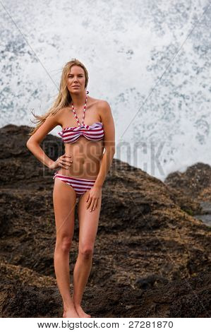 Attractive young woman posing in a bikini on rocks on a beach.  She has one hand on her hip and ocean sea spray is in the background. Vertical shot.