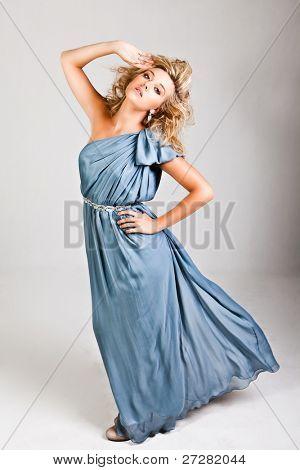 Porträt einer jungen Frau. Ihr Haar ist wild und sie trägt ein blaues Kleid, das aus einer Handtasche ist