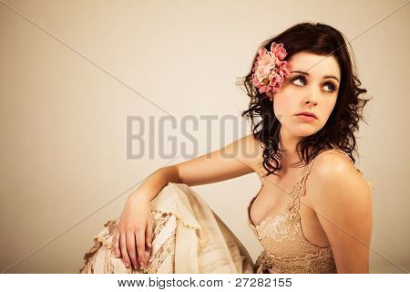 Portrait of a young woman. Her hair is styled with a flower and she is wearing a vintage dress.