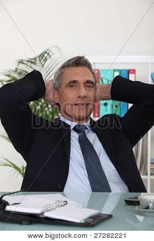 Portrait of an arrogant businessman with his hands behind his head
