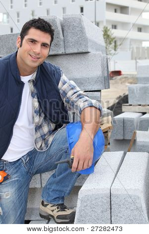 Worker posing with stacks of concrete blocks