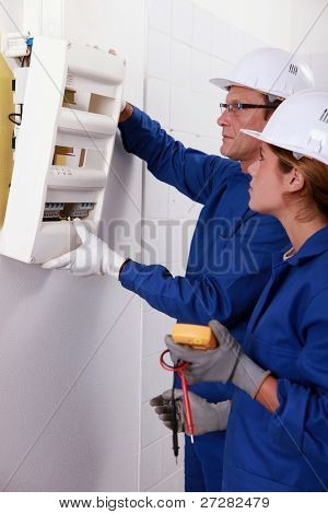 Electrical team installing a fuse box