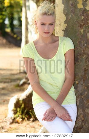 Young woman standing by a plane tree
