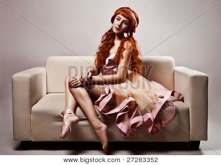 A imagem de uma bela mulher em luxuoso vestido sentado no sofá. Estúdio tiro