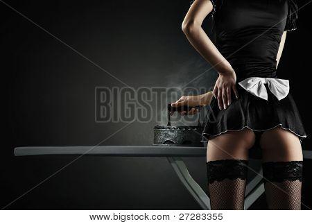 Vintage sexy maid with  retro iron on black background