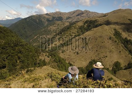 Two people sit on the ground and see beautiful scenery of alpine.